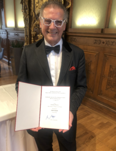 Reinhard Wallner hält die Urkunde mit der Verleihung des Professorentitel von Alexander Van der Bellen in Händen.